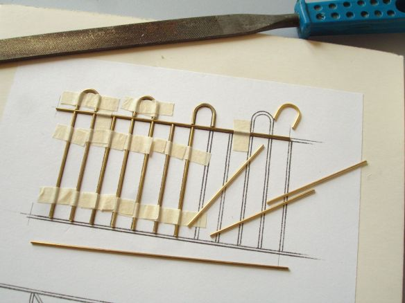 pieces of brass being assembled on a railing template